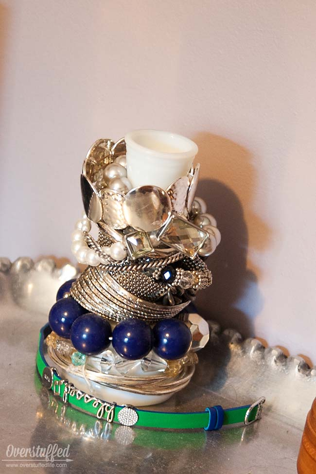 Storing bracelets on a milk glass vase found at a thrift store looks pretty and is functional, too. #overstuffedlife